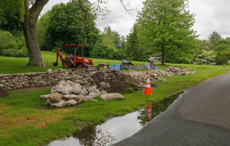 Construcción natural de la pared de piedra con el motor de la tierra en el borde de la carretera imagen de archivo libre de regalías