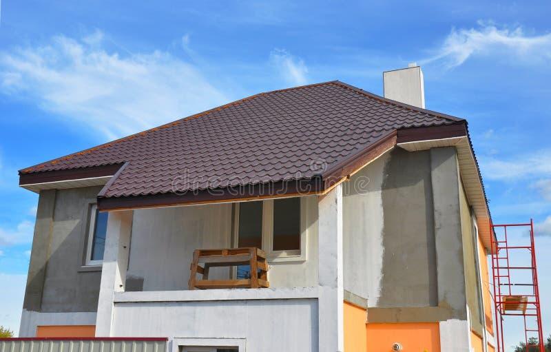 Construcción o reparación de la casa rural con el balcón, aleros, ventanas, chimenea, techumbre, fachada de la fijación, aislamie imagen de archivo libre de regalías