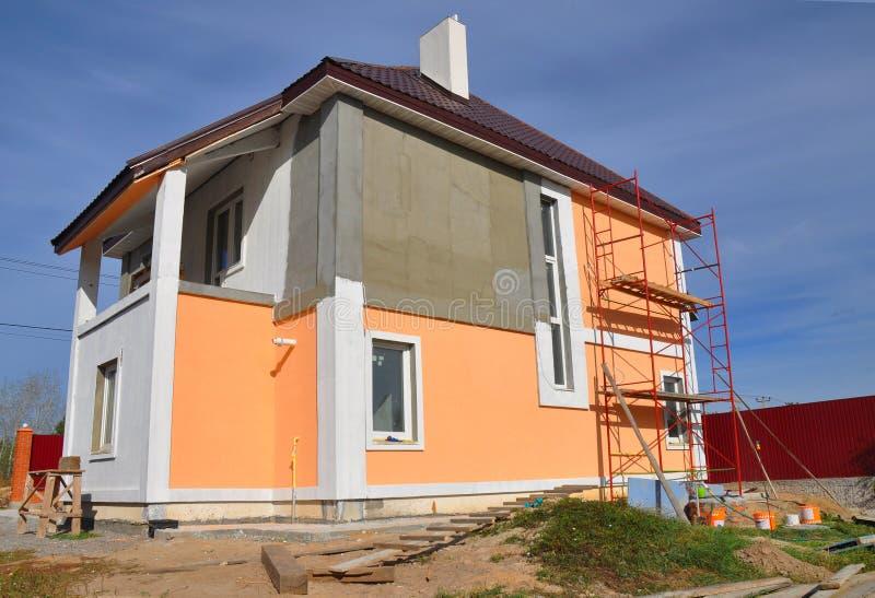 Construcción o reparación de la casa rural con el balcon, los aleros, las ventanas, la chimenea, la techumbre, la fachada de la f foto de archivo