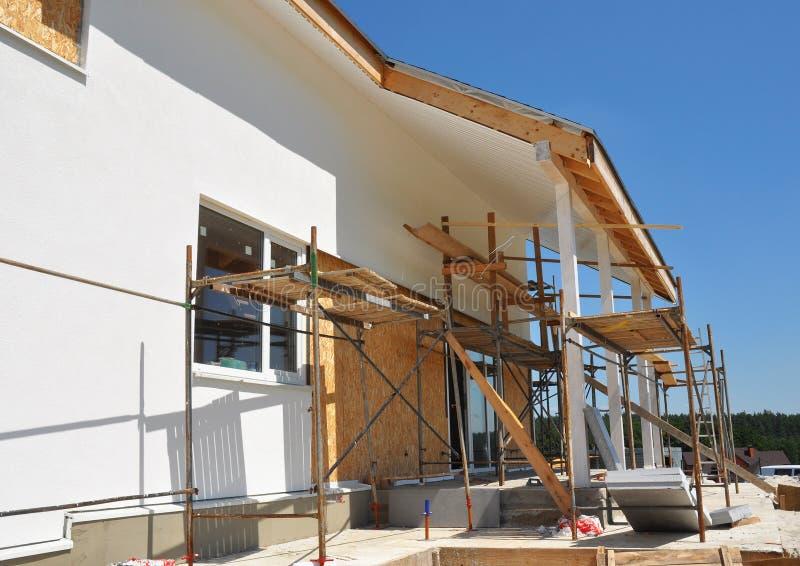 Construcción o reparación de la casa rural con los tragaluces, los aleros, Windows, la casa de fijación de la fachada, del aislam foto de archivo libre de regalías