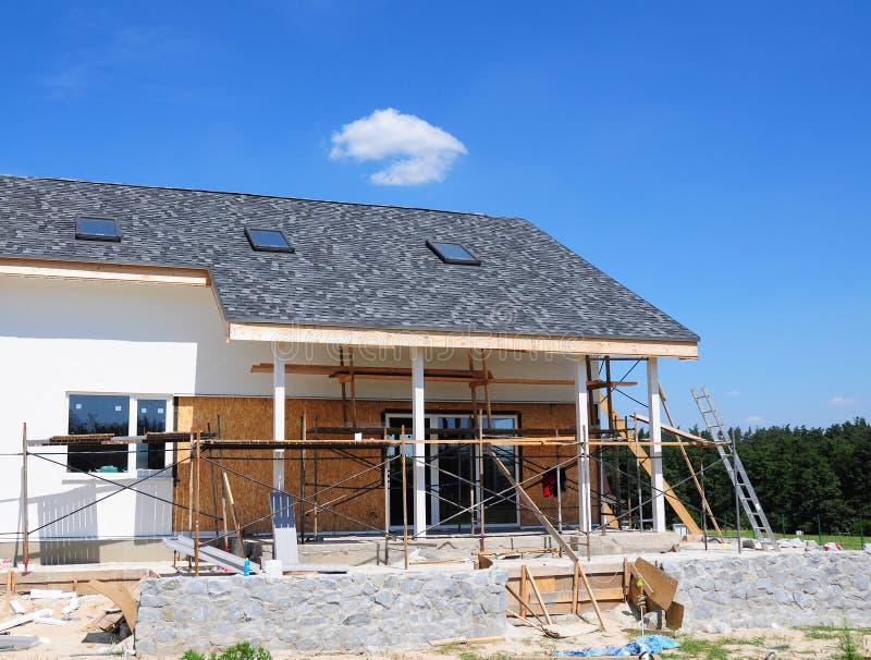 Construcción y renovación de la casa rural con los tragaluces, los aleros, Windows, la fachada de fijación, el aislamiento, la en imagenes de archivo