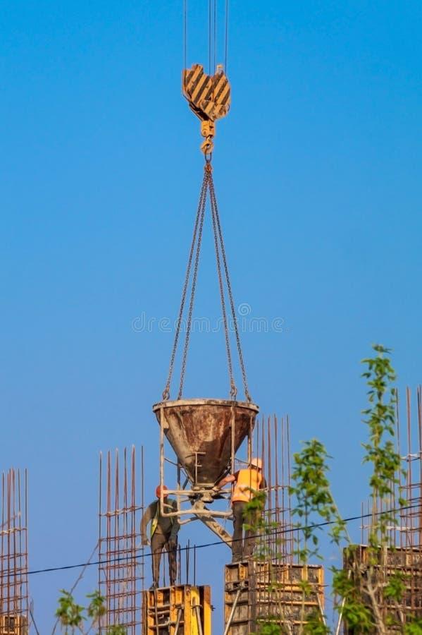 Construcci?n de la casa - los trabajadores concretos sirvieron la gr?a fotos de archivo