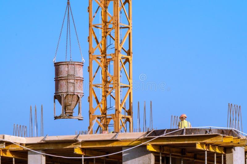 Construcci?n de la casa - los trabajadores concretos sirvieron la gr?a imagenes de archivo