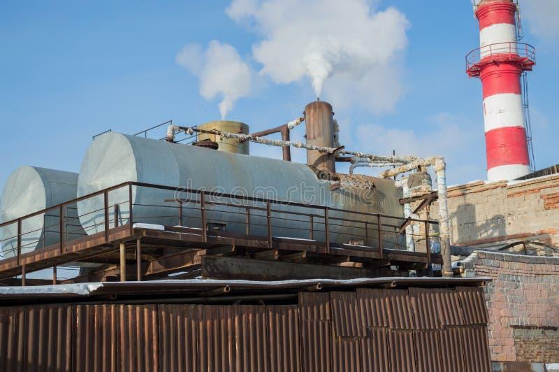 Construcciones del punto del calor con los tanques en una empresa industrial imagenes de archivo