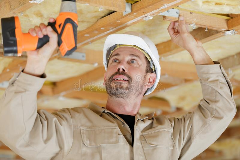 Constructeur ? l'aide de la perceuse sans fil sur les poutrelles en bois de plafond image libre de droits