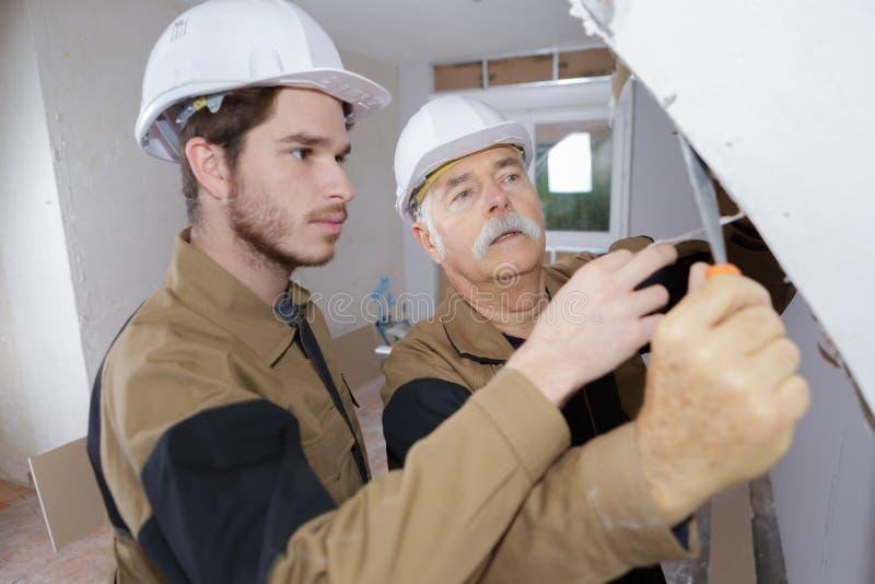 Constructeur avant de plasterering au travail photo stock