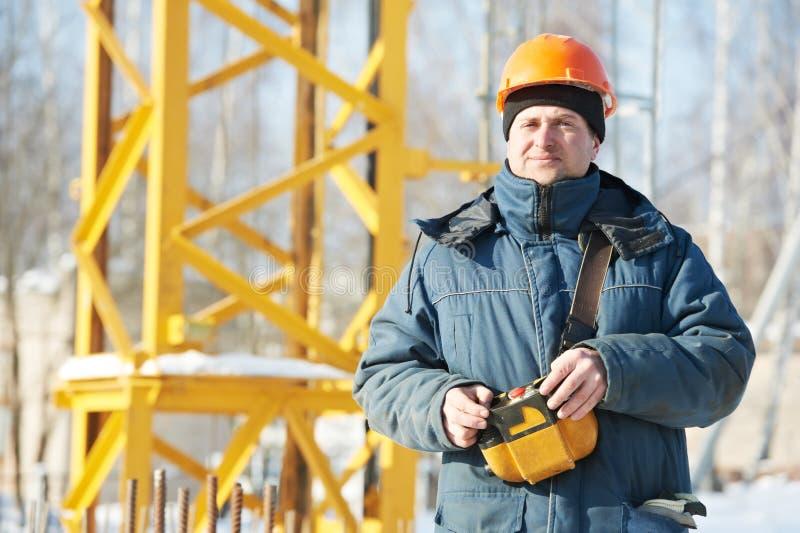 Constructeur avec l'équipement à télécommande de grue à tour photographie stock libre de droits