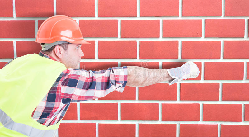 Constructeur beau dans l'équipement de protection agissant comme le héros image stock