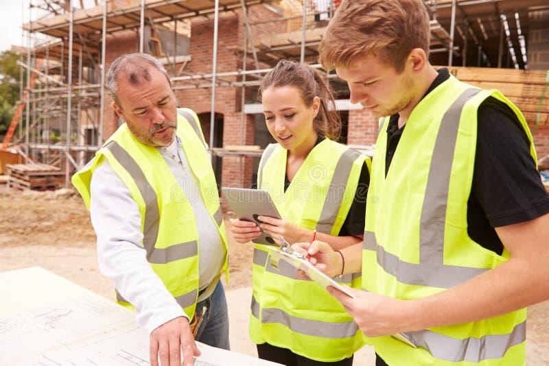 Constructeur On Building Site discutant le travail avec des apprentis photos libres de droits