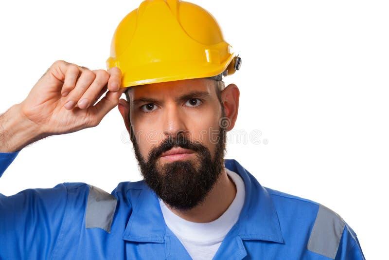 Constructeur dans le casque antichoc, l'agent de maîtrise ou le dépanneur touchant son casque Travailleur barbu d'homme avec la b images libres de droits