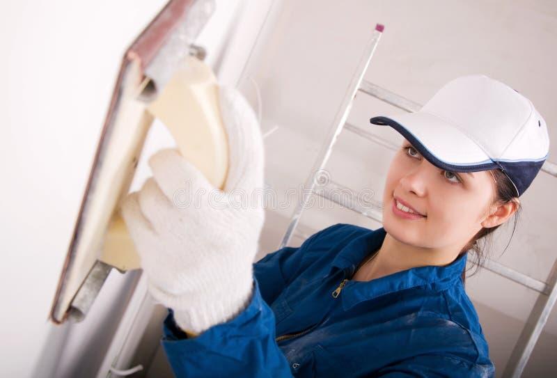 Constructeur de jeune femme polissant le mur image stock