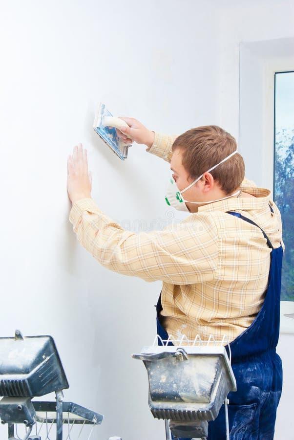Constructeur de jeune homme polissant le mur photo stock