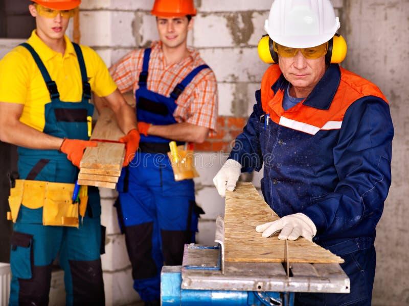 Constructeur de personnes de groupe avec la scie circulaire. photo stock