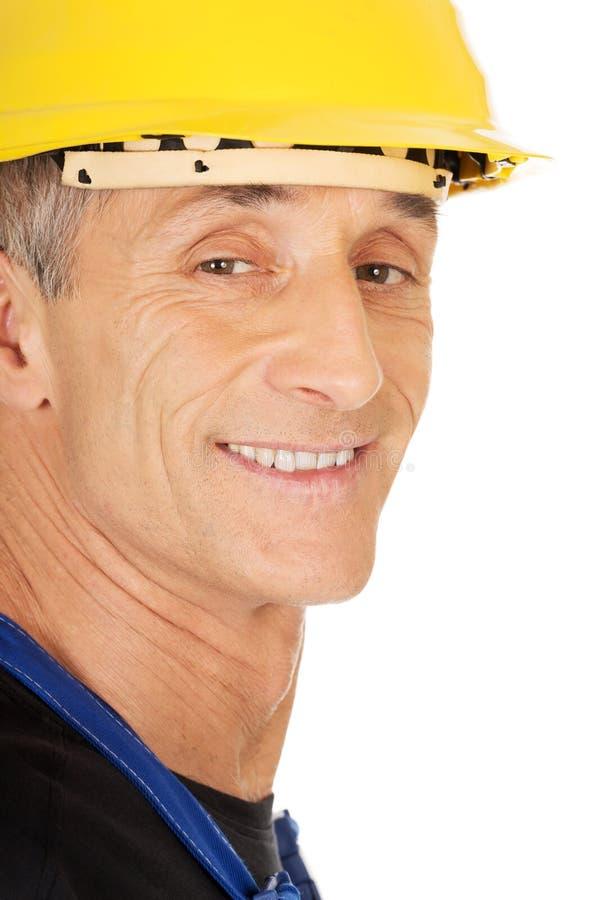 Constructeur de sourire avec un casque de sécurité photographie stock