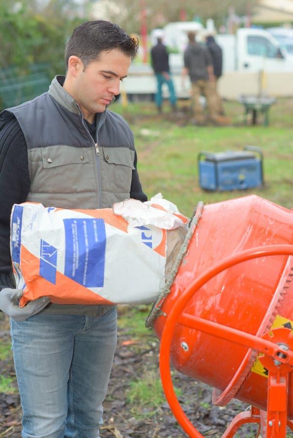 Constructeur faisant le ciment dehors images libres de droits
