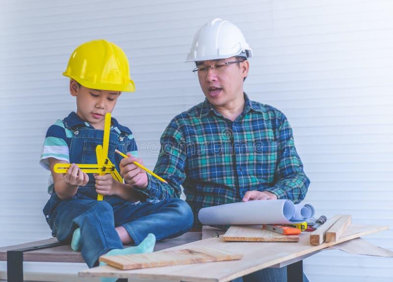 Constructeur Father enseignant son fils ? lire le papier de plan de construction photos stock