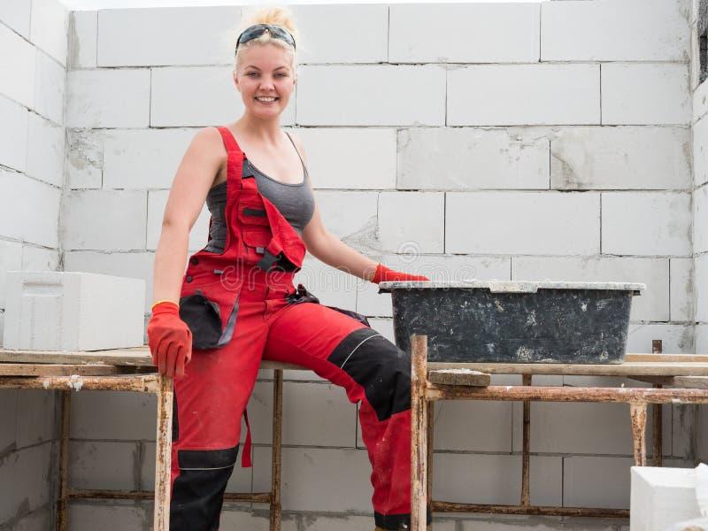 Constructeur femelle fonctionnant pour construire la nouvelle maison photo libre de droits