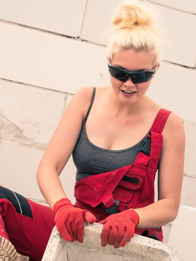 Constructeur femelle fonctionnant pour construire la nouvelle maison photographie stock
