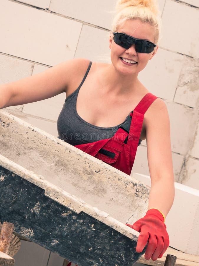 Constructeur femelle fonctionnant pour construire la nouvelle maison photos stock