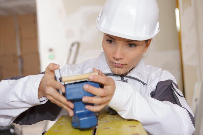 Constructeur femelle préparant la machine de ponçage photo stock