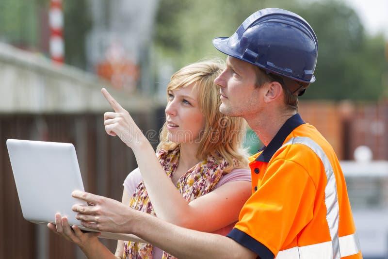 Constructeur, femme et ordinateur portatif image stock