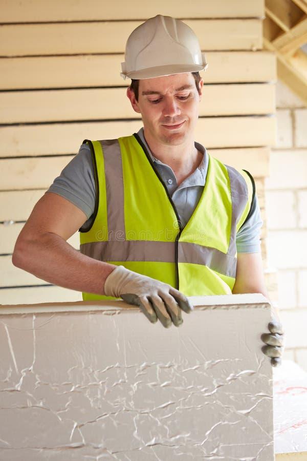 Constructeur Fitting Insulation Boards dans le toit de la nouvelle maison images libres de droits