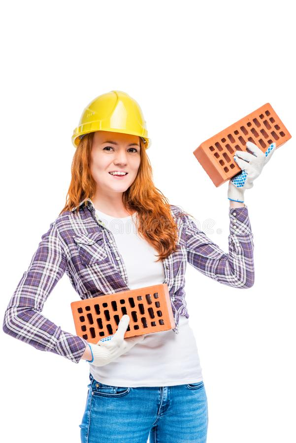 Constructeur fort de femme en brise jaune avec des briques sur le backg blanc photo stock