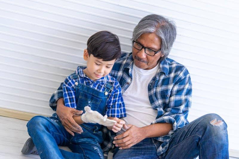 Constructeur Grand Father mettant le gant fonctionnant pour son petit-fils pour le concept de génération de famille photographie stock