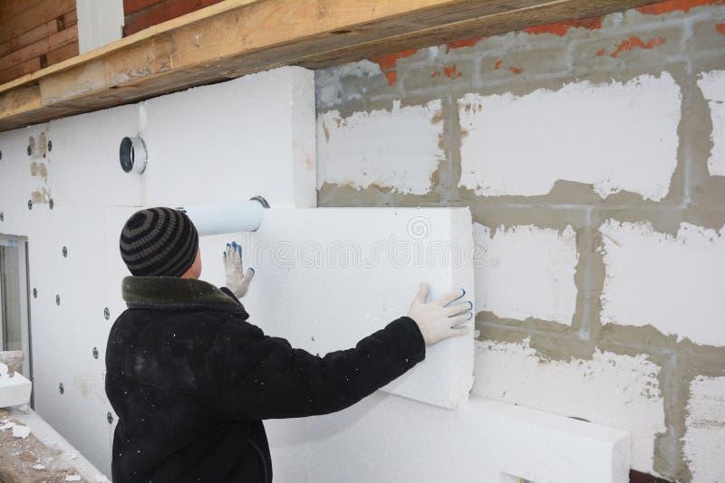 Constructeur installant le panneau isolant rigide de mousse de styrol pour l'économie d'énergie photographie stock