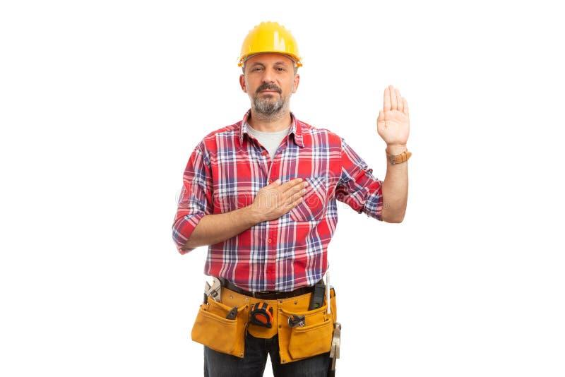 Constructeur jurant avec la paume et la main sur le coeur photographie stock libre de droits