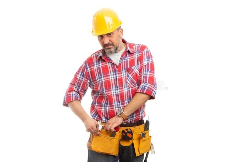 Constructeur mettant la corde à l'intérieur de la poche de ceinture d'outil photo libre de droits