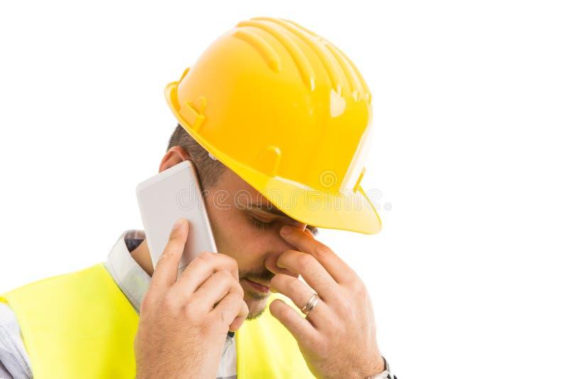 Constructeur ou architecte soumis à une contrainte parlant au téléphone images stock