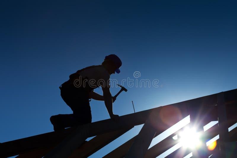 Constructeur ou charpentier travaillant au toit images libres de droits
