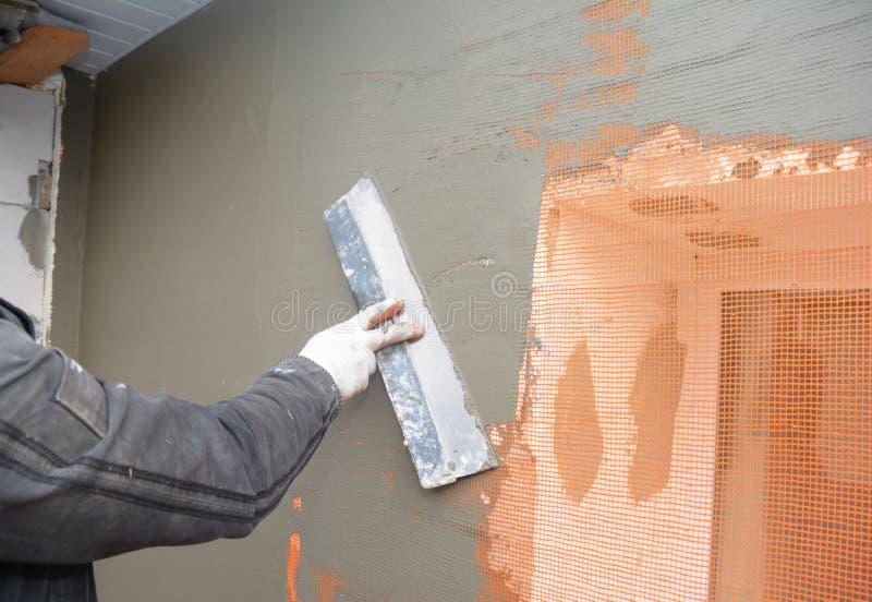 Constructeur plâtrant le mur avec la spatule, maille de fibre de verre, maille de plâtre après isolation rigide de mousse photos libres de droits