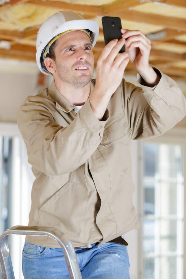 Constructeur prenant la photographie sur le site utilisant le smartphone photos stock