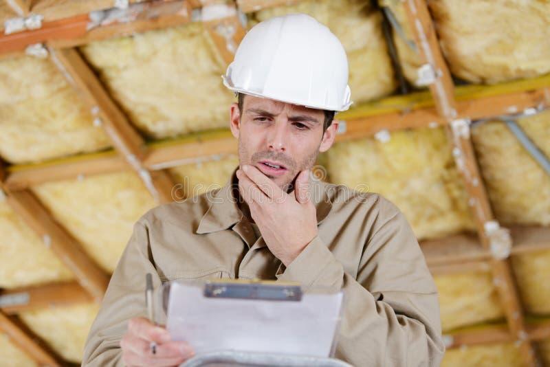 Constructeur regardant le presse-papiers avec l'expression confuse images libres de droits