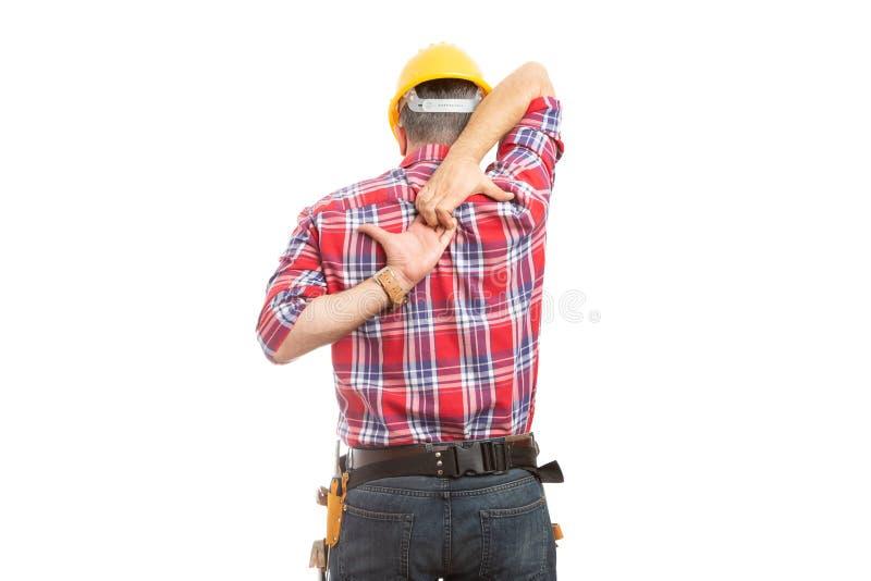 Constructeur s'étirant avec des mains derrière le dos photographie stock libre de droits