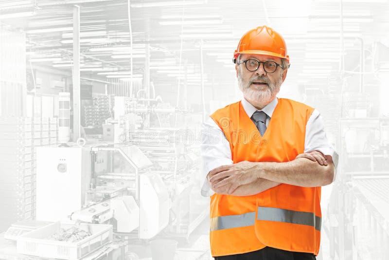 Constructeur supérieur professionnel dans le casque orange sur le fond industriel photo libre de droits