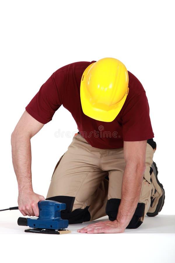Constructeur utilisant la ponceuse sur le plancher images libres de droits