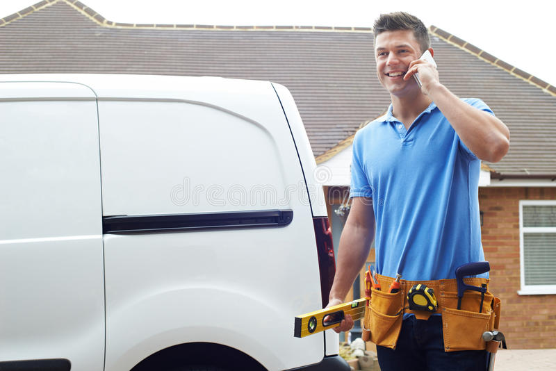 Constructeur With Van Talking On Mobile Phone en dehors de Chambre images stock