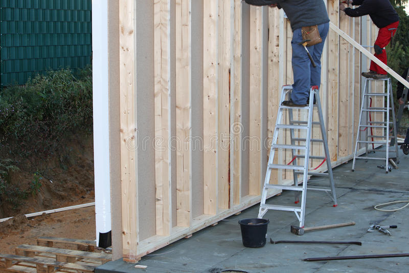 Constructeurs installant une maison de trame de bois de construction images libres de droits