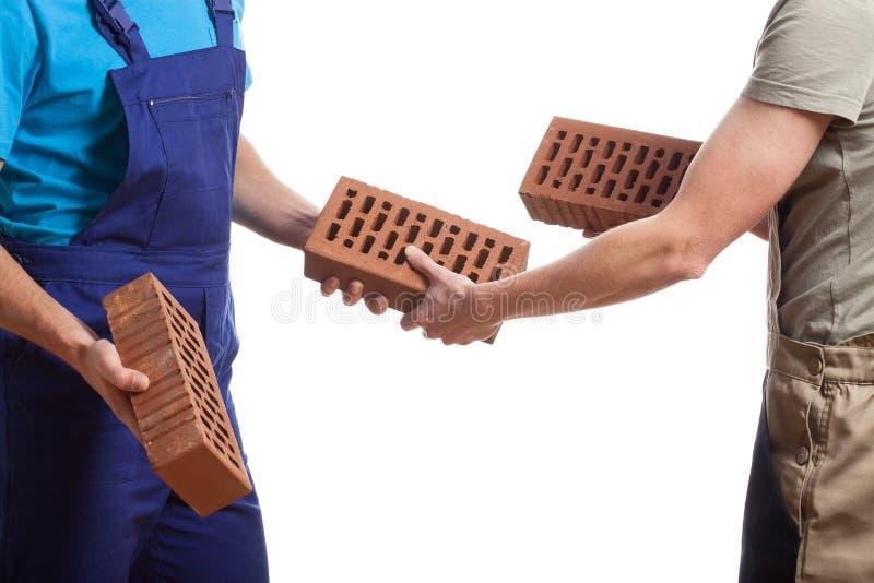 Constructeurs passant des briques photo libre de droits