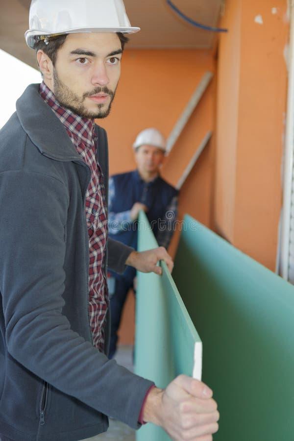 Constructeurs portant les conseils en bois à l'intérieur image stock