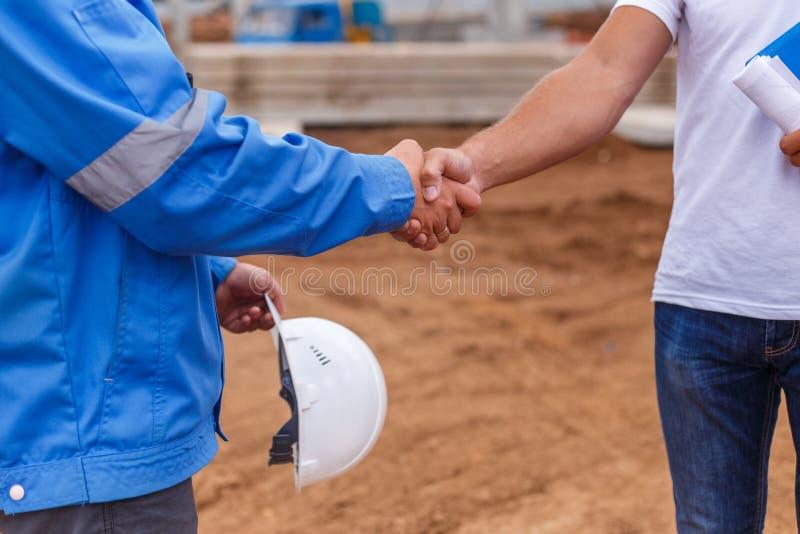 Constructeurs se serrant la main images stock