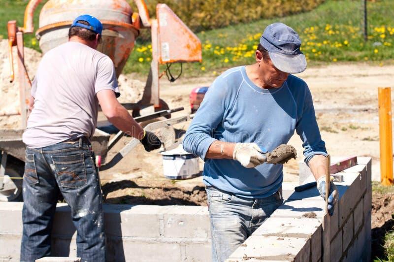 Constructeurs sur le site de maison image libre de droits