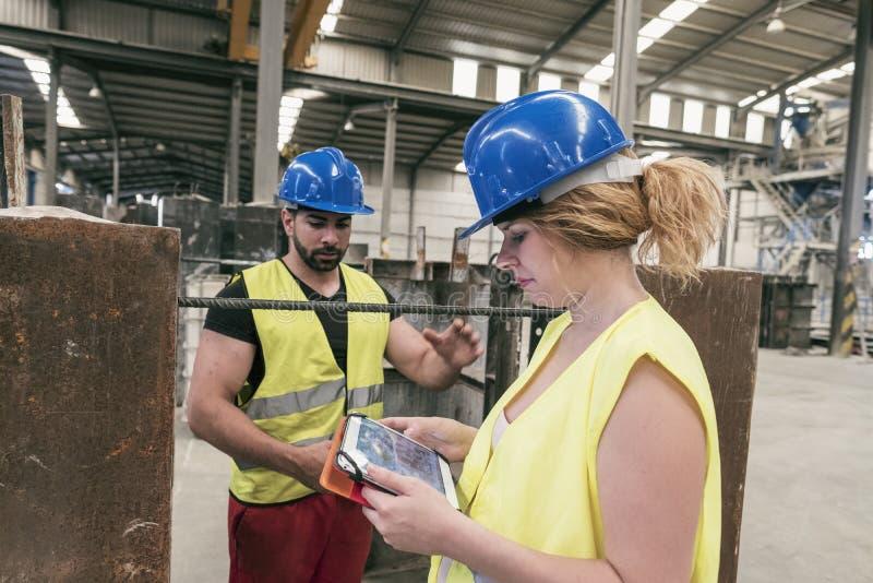 Constructinarbeider die tablet kijken stock foto's