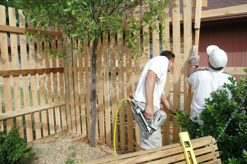 Constructing a Fence. Two men work to build a new fence that will be board on board royalty free stock images