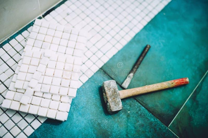 Construction à la maison industrielle - marteau et mosaïque, carreaux de céramique en pierre de marbre blancs photos libres de droits