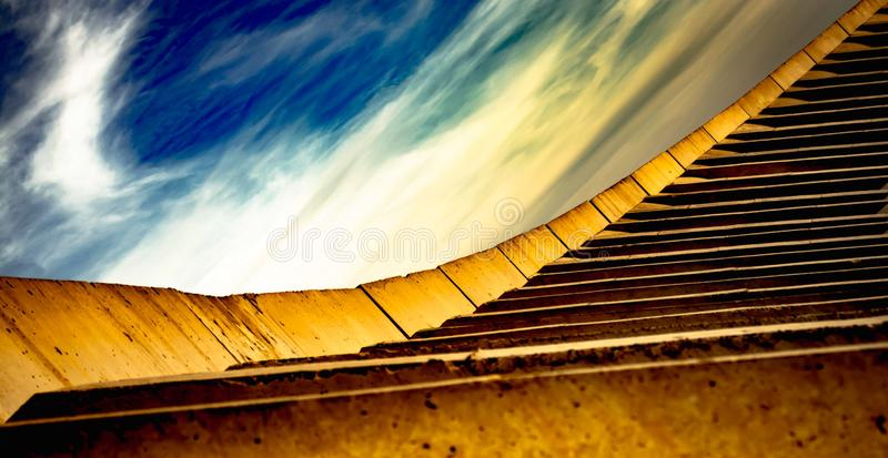 Construction, abstract yellow stairs and beautiful sky with white clouds stock photos