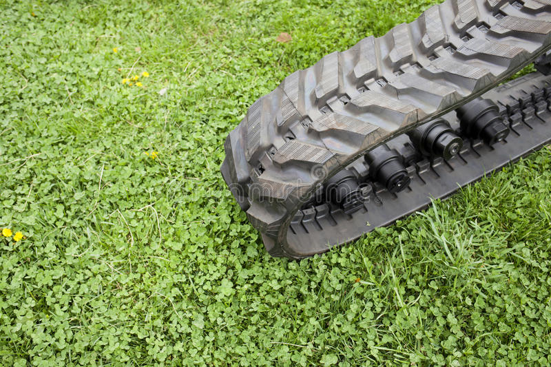 Construction and Agriculture machine with rubber crampons. Detail of machine (construction and agriculture) with rubber crampons on green grass stock photo